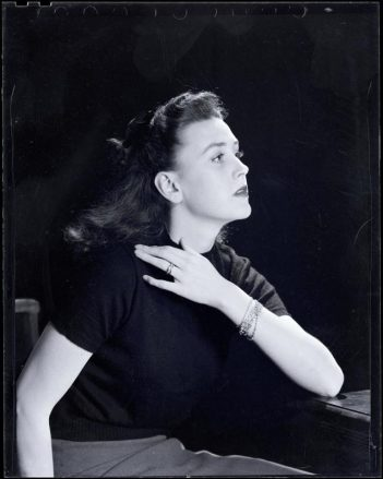 A glamorous black and white photograph of Bridget Bate Tichenor shown seated at a table with her hand resting on her shoulder. Her face is in profile.