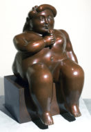 A bronze sculpture of a seated nude girl eating an ice cream cone