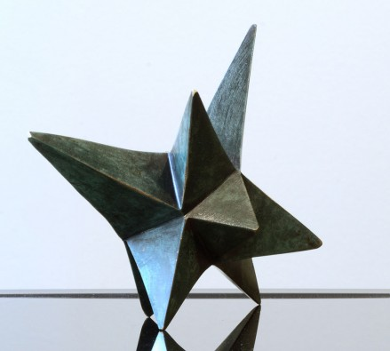 A ten pointed bronze star with a dark green patina. The points of the star are varying lengths