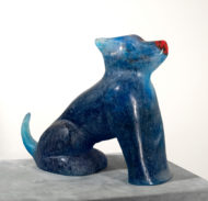 A blue glass sculpture of a seated dog